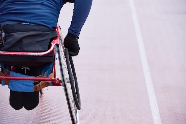 Przygotowanie do paraolimpiady. widok z tyłu fizycznie upośledzonego sportowca poruszającego się w wyścigowym wózku inwalidzkim na torze