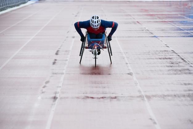 Przygotowanie do paraolimpiady. zdeterminowany zawodnik na wózku inwalidzkim w odzieży sportowej i kasku dojeżdżający do mety podczas treningu na zewnętrznym stadionie lekkoatletycznym