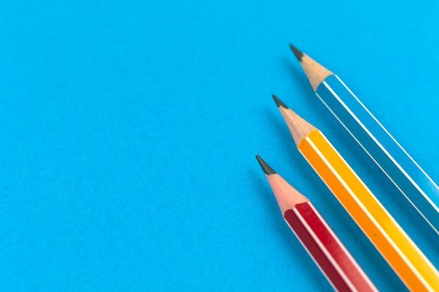 Przygotowanie do pierwszych dni szkoły za pomocą prostych ołówków na płaskim świecącym niebieskim tle, skopiuj zdjęcie przestrzeni
