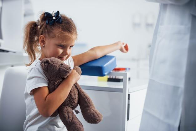 Przygotowanie do pobrania krwi. mała dziewczynka z zabawką w rękach jest w klinice.
