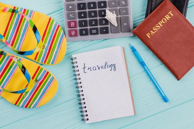 Przygotowanie do podróży i koncepcja flat lay. ołówek, papierowa notatka, kalkulator na niebieskim biurku.