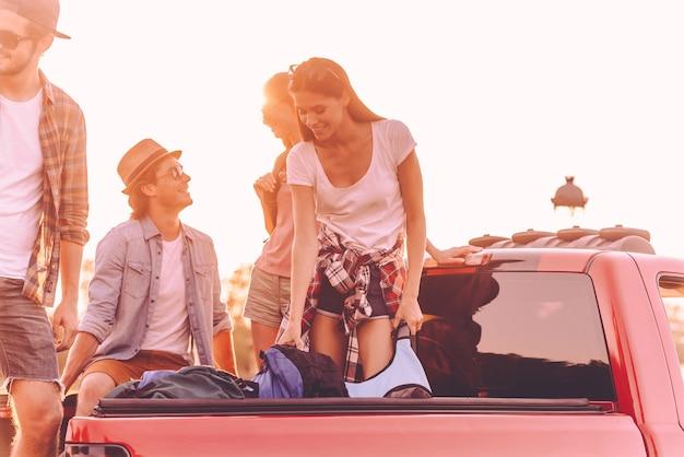 Przygotowanie do podróży. piękni młodzi ludzie ładujący plecaki do pick-upa i wyglądający na szczęśliwych