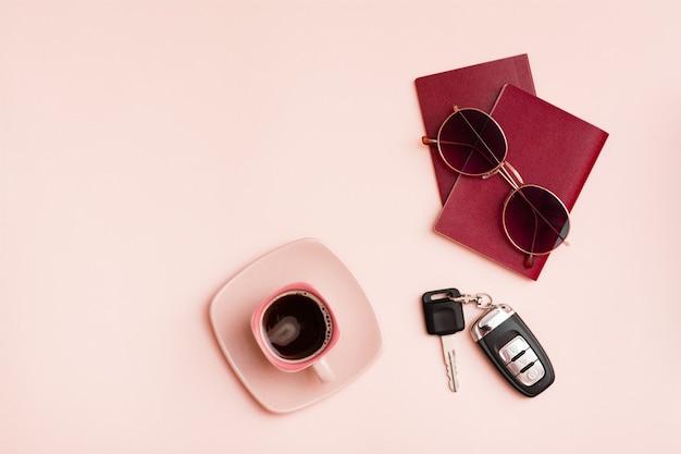 Przygotowanie do podróży samochodem. paszporty, okulary przeciwsłoneczne, kluczyki do samochodu i filiżanka kawy na różowym tle. turystyka lokalna. widok z góry. skopiuj miejsce