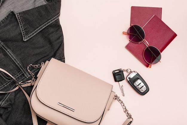 Przygotowanie do podróży samochodem. paszporty, okulary przeciwsłoneczne, kluczyki do samochodu, torba i dżinsowa kurtka na różowym tle. turystyka lokalna. widok z góry