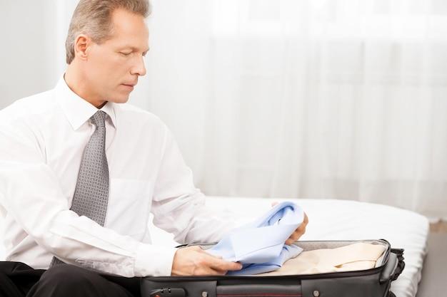 Przygotowanie do podróży służbowej. pewny siebie siwy mężczyzna w koszuli i krawacie, pakujący swój bagaż, siedząc na łóżku