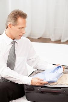 Przygotowanie do podróży służbowej. pewny siebie starszy mężczyzna w koszuli i krawacie, pakujący swój bagaż, siedząc na łóżku