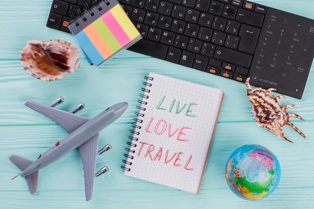 Przygotowanie do podróży, wakacje wycieczka, turystyka makieta samolotu, muszle, naklejki, kula ziemska na lazurowym drewnianym stole. czarna klawiatura komputerowa.