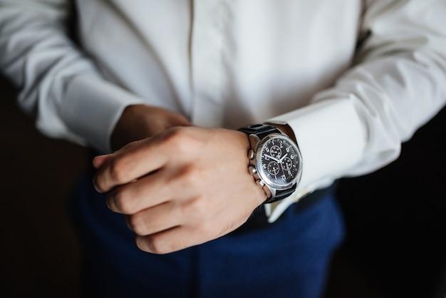 Przygotowanie do prób. zegarek pana młodego pod ręką.