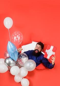Przygotowanie do przyjęcia urodzinowego uśmiechnięty mężczyzna patrzący przez papierową dziurkę trzyma balony i przyjęcie prezentowe