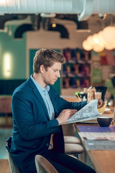 Przygotowanie do spotkania. biznes młody poważny człowiek patrzący na plan budowy w folderze siedzący z kawą w kawiarni czekając na spotkanie