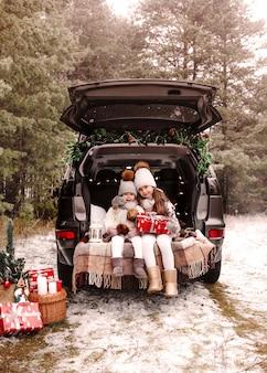 Przygotowanie do świąt. nastoletnie dzieci cieszą się prezentem świątecznym w bagażniku samochodu. mroźna zima, śnieżna pogoda.