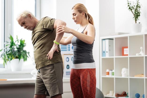 Przygotowanie do treningu. ładna poważna kobieta stojąca w sali do ćwiczeń, przygotowująca się do treningu ze swoim pacjentem