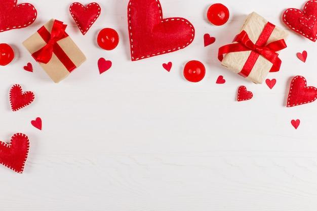 Przygotowanie do walentynek. czerwoni serca i rzemiosło prezenty na białym drewnie. skopiuj miejsce