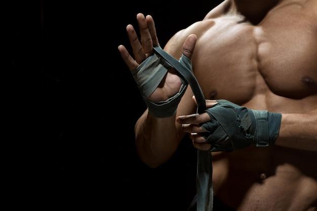 Przygotowanie do walki. przycięte ujęcie młodego boksera jodłowego przygotowującego bandaże do walki na czarno