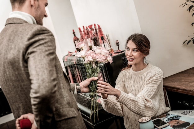 Przygotowanie do złożenia oferty. kobieta otrzymująca bukiet kwiatów przed otrzymaniem propozycji