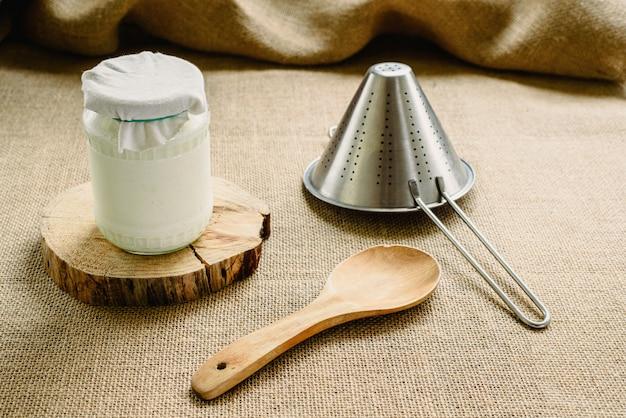 Przygotowanie domowego kefiru mlecznego, oddzielanie ziaren od mleka w celu uzyskania naturalnego jogurtu o kwasowym smaku.