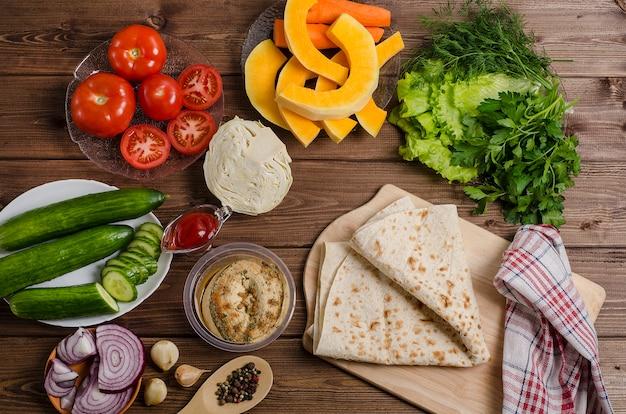 Przygotowanie domowej roboty wegetariańskiej shawarma z hummusem i warzywami na ciemnym drewnianym tle