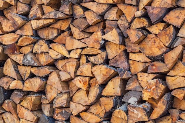 Przygotowanie drewna opałowego na zimę. drewno opałowe tło, stosy drewna opałowego w lesie