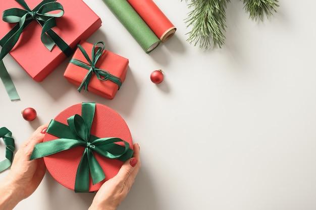 Przygotowanie i pakowanie świątecznego, czerwonego i zielonego pudełka na prezenty na święta