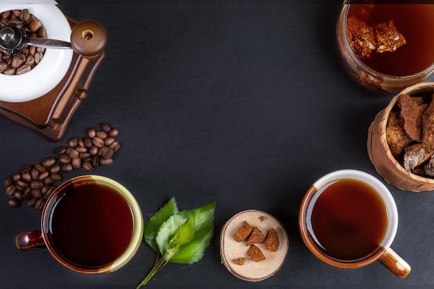 Przygotowanie kawa grzybowa chaga. filiżanki, słoik z napojem chaga, młynek do kawy, kawałki chaga i ziarna kawy na czarno.