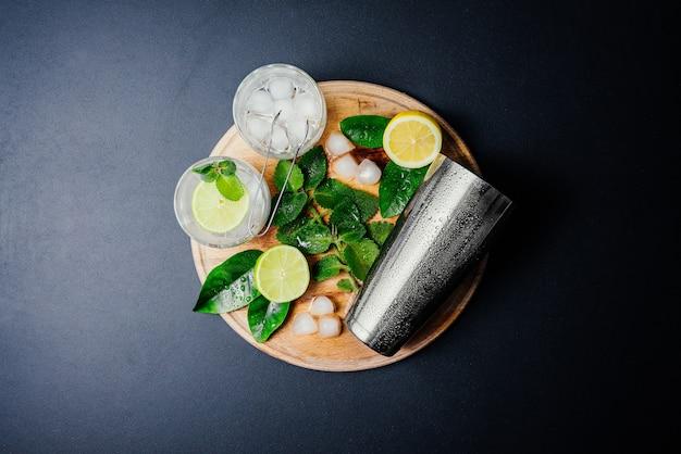 Przygotowanie koktajli mojito. mięta, limonka, cytryna, składniki lodowe i naczynia barowe.