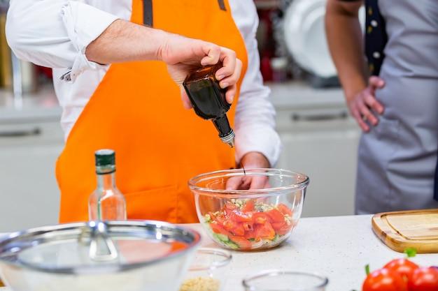 Przygotowanie kuchni: szef kuchni przygotowuje sałatkę