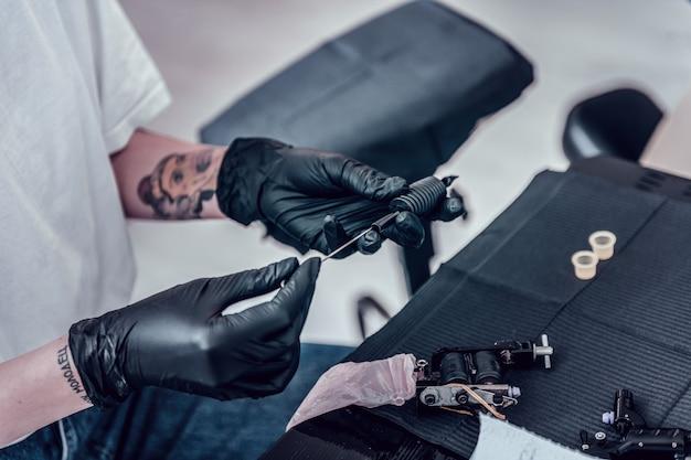 Przygotowanie maszyny atramentowej. profesjonalny mistrz tatuażu ustawiający igłę wewnątrz maszyny do tatuażu i konstruując wszystkie szczegóły razem