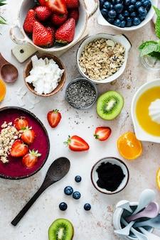 Przygotowanie miski acai w stylu flat lay z tropikalnymi owocami i ziarnami
