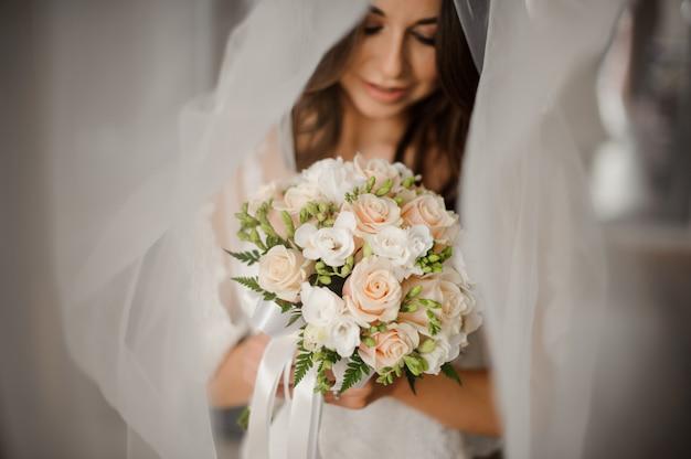 Przygotowanie narzeczonej rano. portret pięknej narzeczonej w białej zasłonie z bukietem ślubnym