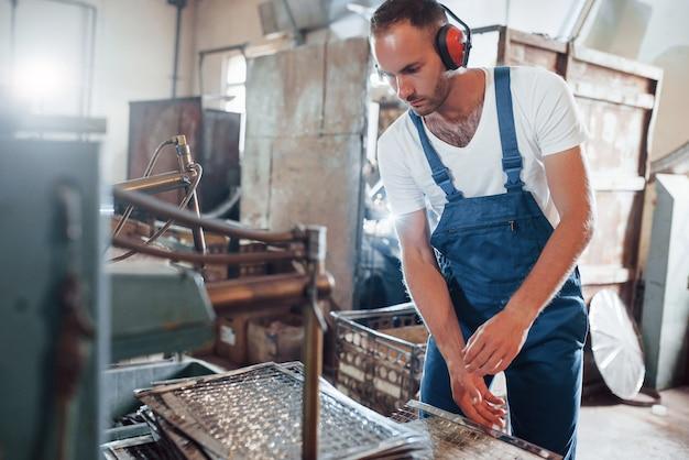 Przygotowanie niektórych materiałów do produkcji. mężczyzna w mundurze pracuje nad produkcją. nowoczesna technologia przemysłowa.