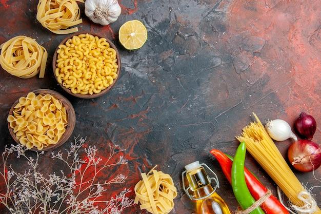 Przygotowanie obiadu z surowego makaronu, papryki cayenne, połączonych ze sobą sznurkiem, butelki oleju, cytryny, czosnku, na stole o różnych kolorach