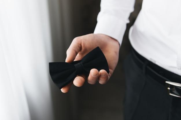Przygotowanie pana młodego rano, przystojny pan młody z motylem ubiera się i przygotowuje do ślubu