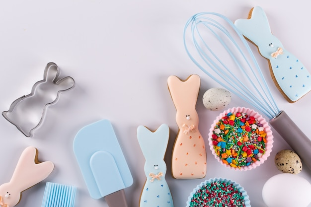 Przygotowanie pierników. wielkanocne ciasteczka w kształcie zabawnego królika, narzędzia niezbędne do zrobienia piernika, kolorowe posypki. wielkanocna koncepcja.