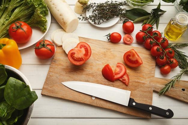 Przygotowanie sałatki ze świeżych warzyw w kuchni tabeli widok z góry. cięcie pomidorów i rzepy na drewnianej desce, kopia przestrzeń