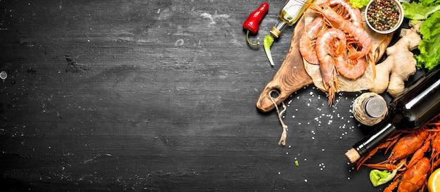 Przygotowanie świeżych owoców morza. wino z przyprawami i świeżymi krewetkami, homarem. na czarnej tablicy.