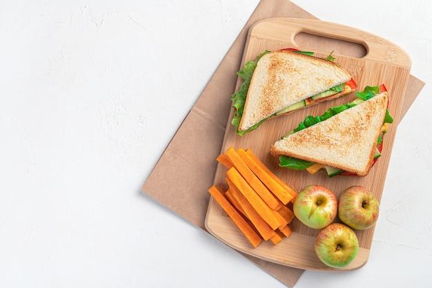 Przygotowanie szkolnej kanapki śniadaniowej marchewki i jabłka na desce do krojenia na szarym tle