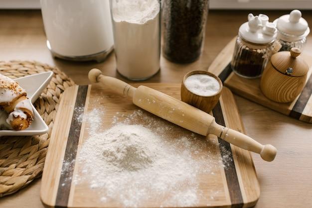 Przygotowanie testu. składniki na ciasto, mąka z wałkiem na drewnianym stole. selektywna ostrość