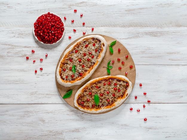 Przygotowanie tradycyjnego arabskiego pizzy z mięsem i granatem.