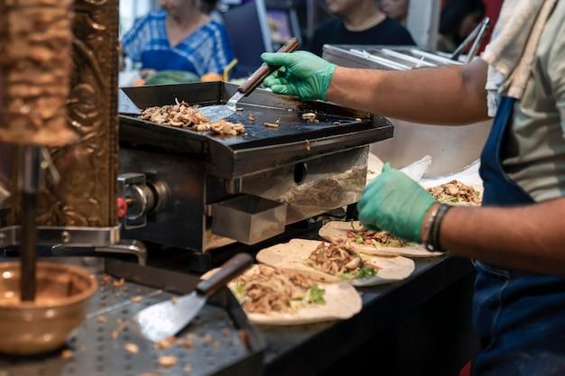 Przygotowanie tureckiej shawarmy kucharze rękoma w gumowych rękawiczkach nakładają pyszny posiekany smażony chi...