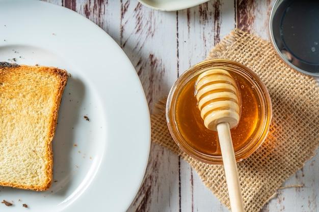 Przygotowanie zdrowego śniadania z grzanką z masłem i czystym ekologicznym miodem pszczelim. koncepcja zdrowej żywności.