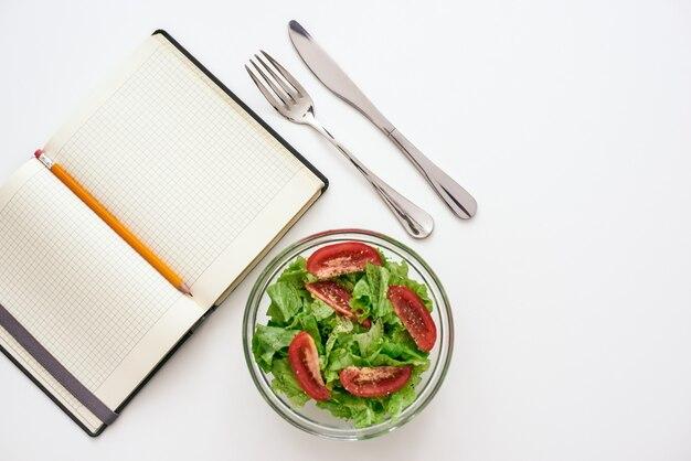 Przygotowanie zdrowej żywności. widok z góry na książkę kucharską na przepis, w pobliżu sałatka, na białym tle. widelec i nóż przy talerzu