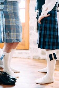 Przygotowując się do szkockiego wesela, naprzeciw siebie stoją dwaj mężczyźni w sporransowych kiltach i wysokich skarpetkach