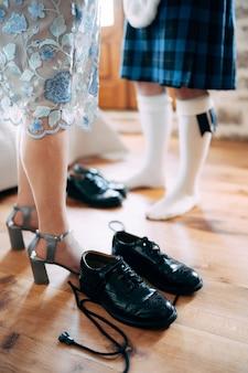 Przygotowujący się do szkockiego ślubu mężczyzna w kilcie i sporranie stoi obok kobiety w spódnicy i