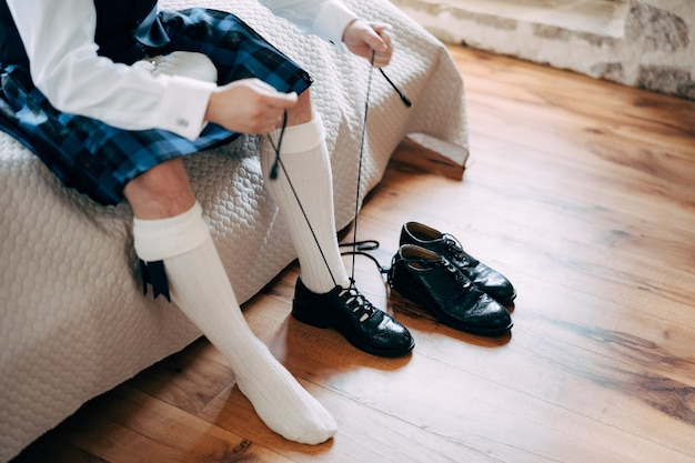 Przygotowujący się do szkockiego wesela mężczyzna w kilcie z sporranem i wysokich skarpetkach siedzi na łóżku i zawiązuje długo