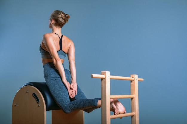 Przygotowywana jest piękna pozytywna blond kobieta, wykonując ćwiczenia pilates, trenując na sprzęcie beczkowym. koncepcja fitness ,, zdrowy styl życia, plastik. skopiuj miejsce, baner sportowy na reklamę.