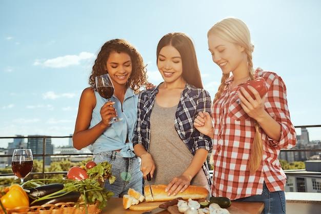 Przygotowywanie jedzenia na piknik trzy młode i wesołe kobiety w zwykłych ubraniach przygotowujące jedzenie