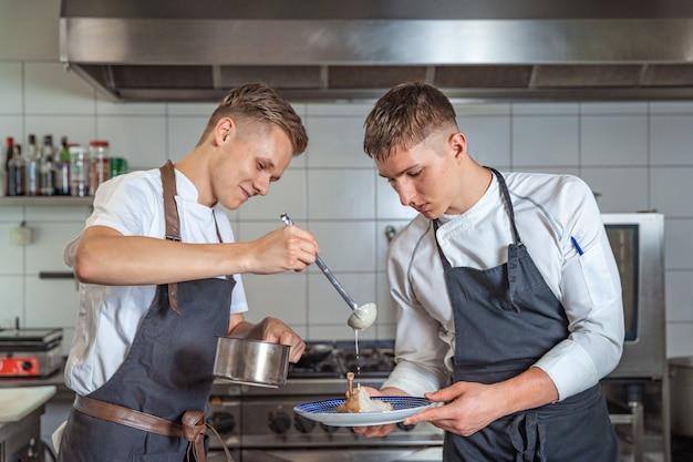 Przygotowywanie mięsa z sosem przez dwóch młodych szefów kuchni