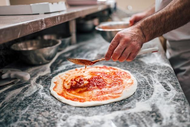 Przygotowywanie pizzy. ręka szefa kuchni dodająca sos pomidorowy na ciasto do pizzy.
