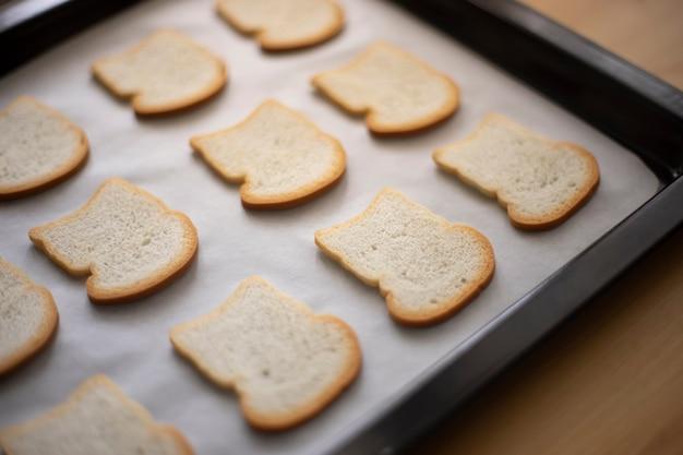Przygotowywanie pokrojonego chleba tostowego na blasze piekarnika