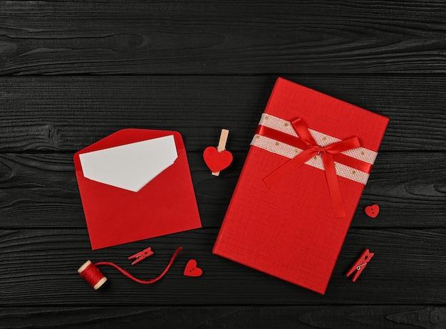 Przygotowywanie prezentów walentynkowych, czerwonych pudełek, serc, sznurka, spinaczy do bielizny i notatki w papierowej kopercie na tle czarnego drewnianego stołu, zbliżenie płasko leżącego, podwyższony widok z góry, bezpośrednio nad